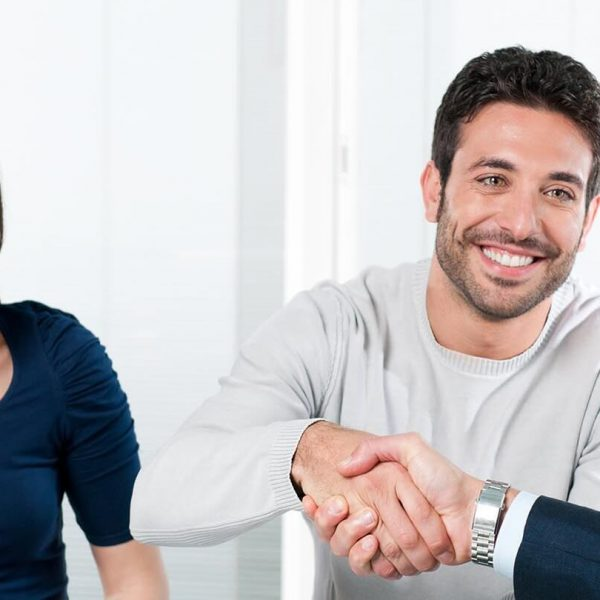 Happy couple seal a deal with their personal financial advisor at home